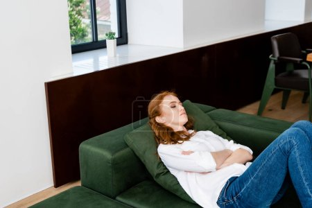 Depressed woman with crossed arms lying on couch