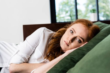 Photo for Selective focus of sad woman looking at camera while lying on sofa at home - Royalty Free Image