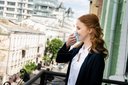 Photo for Side view of smiling woman holding medical mask on terrace - Royalty Free Image