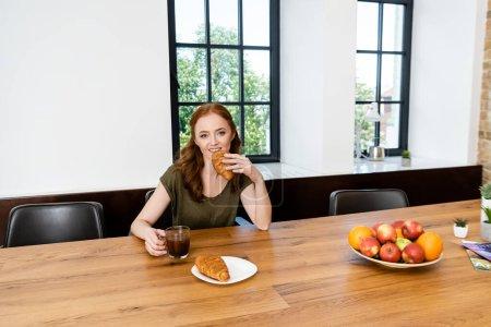 Rothaarige Frau isst Croissant mit einer Tasse Kaffee zu Hause