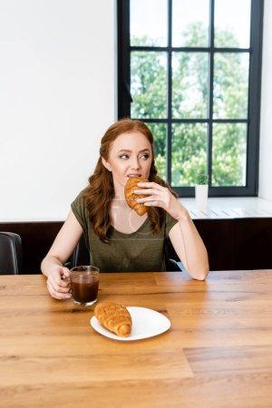 Selektiver Fokus der Frau, die Croissant isst und Kaffeetasse am Tisch hält