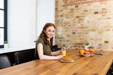 Photo pour Femme souriante regardant la caméra tout en utilisant un smartphone près du petit déjeuner sur la table - image libre de droit