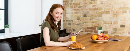 Photo for Horizontal crop of smiling woman using smartphone near croissants and orange juice on table - Royalty Free Image