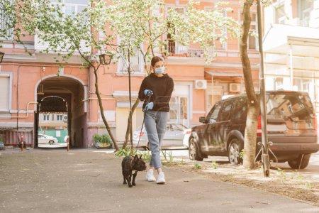 Photo pour Jeune femme dans masque médical marche avec mignon bouledogue français sur la rue - image libre de droit