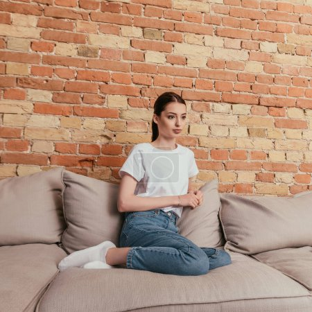 Photo for Attractive young woman sitting on sofa in living room - Royalty Free Image
