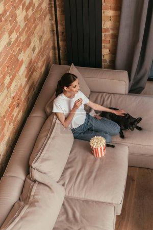 Overhead-Ansicht der fröhlichen Frau auf dem Sofa in der Nähe von Popcorn-Eimer und süße französische Bulldogge sitzen, während Film ansehen