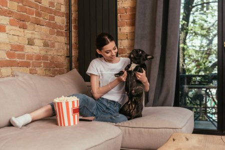 happy girl sitting on sofa near popcorn bucket and touching cute french bulldog