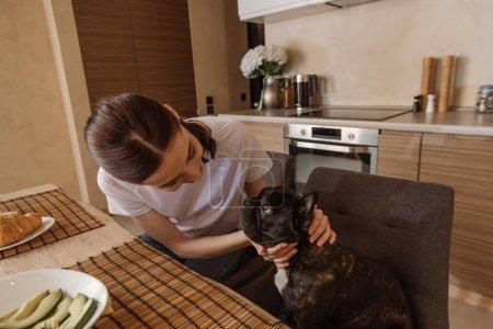 Photo pour Jeune femme touchant bulldog français près de savoureux petit déjeuner sur la table - image libre de droit