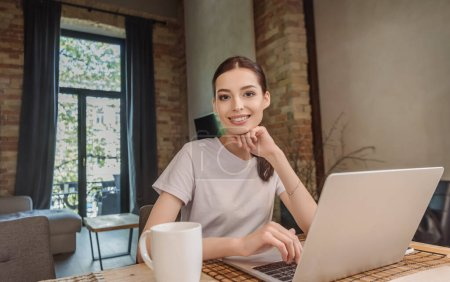 Photo for Happy freelancer looking at camera near laptop and cup of coffee - Royalty Free Image