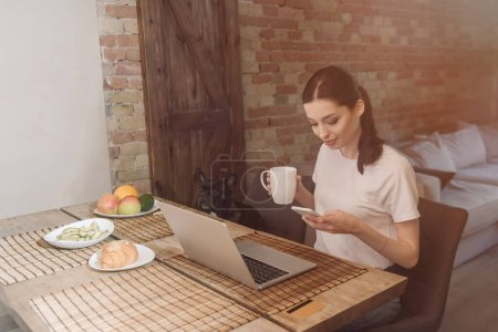 Photo for Attractive freelancer using smartphone near laptop, breakfast and french bulldog - Royalty Free Image