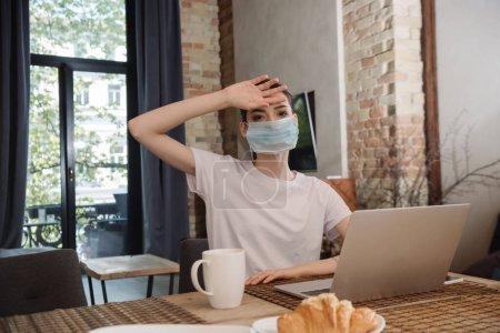 Photo pour Jeune pigiste en masque médical touchant le front près d'un ordinateur portable - image libre de droit
