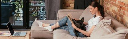 Photo pour Récolte panoramique de livre de lecture heureuse jeune femme près de bouledogue français noir et ordinateur portable avec écran blanc - image libre de droit
