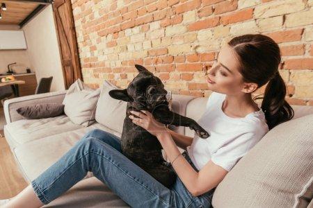 Photo pour Femme heureuse assise sur le canapé et touchant bouledogue français mignon - image libre de droit