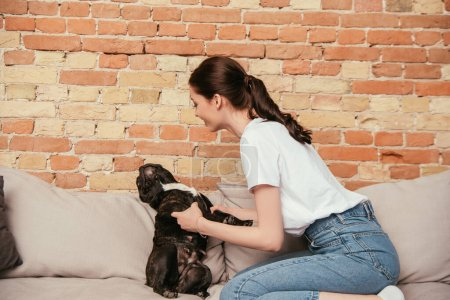 happy woman playing with cute french bulldog in living room