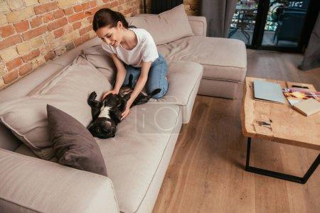 Foto de Alegre chica jugando con lindo bulldog francés en sofá en moderno salón - Imagen libre de derechos