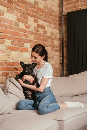 happy young woman hugging cute french bulldog in living room