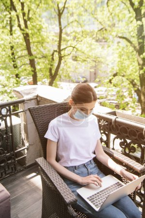Photo for Young freelancer in blue medical mask sitting on chair and using laptop on balcony - Royalty Free Image