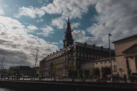 Photo for COPENHAGEN, DENMARK - APRIL 30, 2020: Urban street with Christiansborg Palace tower and cloudy sky at background - Royalty Free Image
