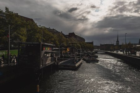 Photo for COPENHAGEN, DENMARK - APRIL 30, 2020: Boats on canal water with urban street and cloudy sky at background - Royalty Free Image