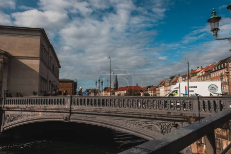 Photo pour COPENHAGUE, DANEMARK - 30 AVRIL 2020 : Des gens marchent sur un pont avec des bâtiments et un ciel nuageux en arrière-plan - image libre de droit