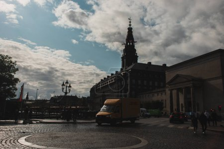 Photo for COPENHAGEN, DENMARK - APRIL 30, 2020: People walking on street with Christiansborg Palace and cloudy sky at background - Royalty Free Image