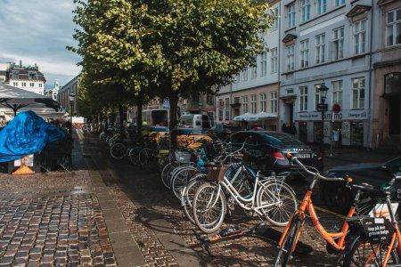 Photo pour COPENHAGUE, DANEMARK - 30 AVRIL 2020 : Vélos près de la route dans une rue urbaine ensoleillée - image libre de droit