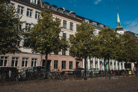Photo pour COPENHAGUE, DANEMARK - 30 AVRIL 2020 : Vélos près des arbres dans la rue urbaine avec bâtiments et ciel bleu en arrière-plan - image libre de droit