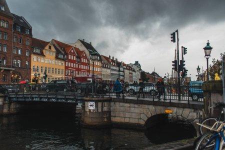 Photo pour COPENHAGUE, DANEMARK - 30 AVRIL 2020 : Des gens marchent sur un pont près du canal avec la rue urbaine Nyhavn et un ciel nuageux en arrière-plan - image libre de droit