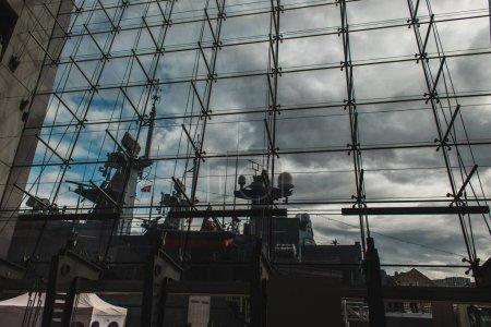 Photo pour COPENHAGUE, DANEMARK - 30 AVRIL 2020 : Navire dans le port près de la façade de la bibliothèque royale danoise avec un ciel nuageux en arrière-plan - image libre de droit