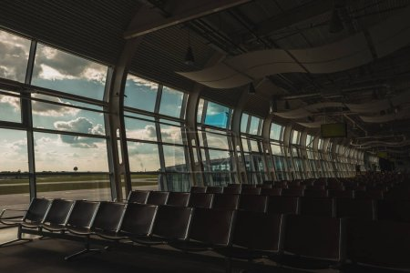 Photo for Chairs in waiting hall of airport with cloudy sky at background - Royalty Free Image