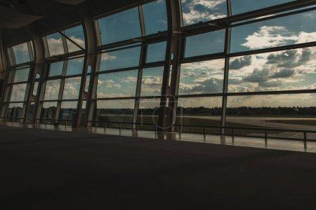 Photo pour Fenêtres d'aéroport avec ciel nuageux et aérodrome en arrière-plan à Copenhague, Danemark - image libre de droit