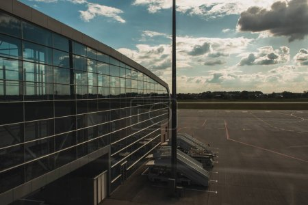 Photo for Glass facade of airport with aerodrome and cloudy sky at background in Copenhagen, Denmark - Royalty Free Image