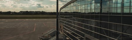 Panoramic shot of glass facade of airport with airfield and cloudy sky at background in Copenhagen, Denmark