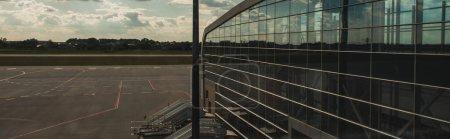 Photo pour Vue panoramique de la façade vitrée de l'aéroport avec aérodrome et ciel nuageux en arrière-plan à Copenhague, Danemark - image libre de droit