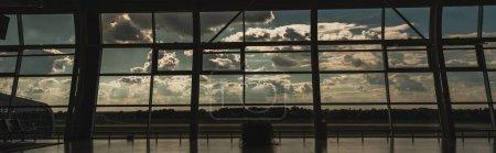 Photo pour Orientation panoramique des fenêtres dans la salle d'attente de l'aéroport avec ciel nuageux en arrière-plan à Copenhague, Danemark - image libre de droit