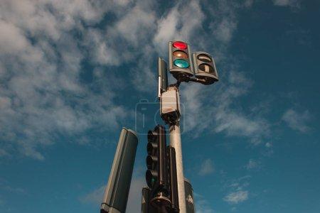 Низкий угол обзора светофоров с облачным небом на заднем плане