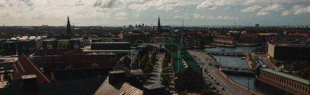 Photo pour Récolte panoramique de toits de bâtiments et de canaux avec ciel nuageux en arrière-plan à Copenhague, Danemark - image libre de droit