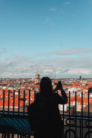 Photo pour Vue arrière du touriste prenant des photos sur smartphone avec des bâtiments et ciel nuageux en arrière-plan à Copenhague, Danemark - image libre de droit