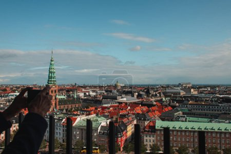Photo for Cropped view of man taking photo with smartphone with buildings of Copenhagen city at background, Denmark - Royalty Free Image