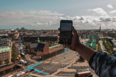 Cropped view of tourist taking picture on smartphone with Copenhagen city at background, Denmark