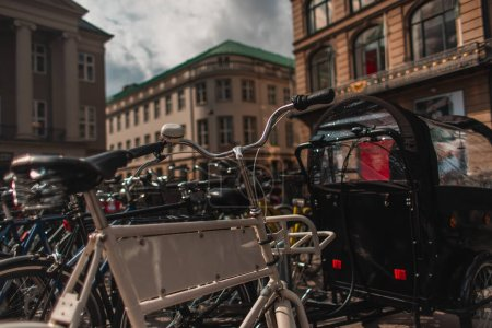 Photo for Selective focus of bicycles on urban street with buildings at background in Copenhagen, Denmark - Royalty Free Image