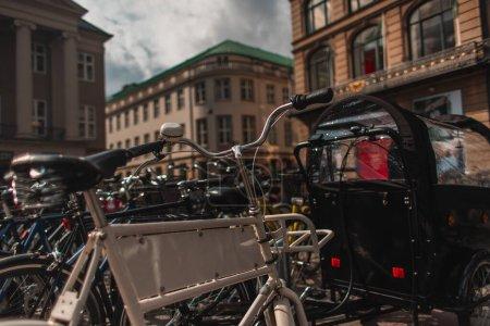 Photo pour Concentration sélective des vélos sur la rue urbaine avec des bâtiments à l'arrière-plan à Copenhague, Danemark - image libre de droit
