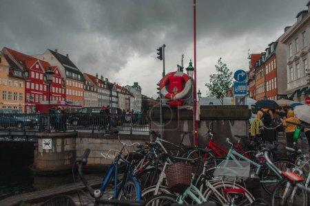Photo pour COPENHAGUE, DANEMARK - 30 AVRIL 2020 : Vélos près du canal sur le port de Nyhavn avec ciel nuageux en arrière-plan - image libre de droit