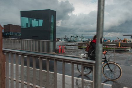 Photo pour Concentration sélective du vélo féminin sur la rue urbaine pendant la pluie à Copenhague, Danemark - image libre de droit