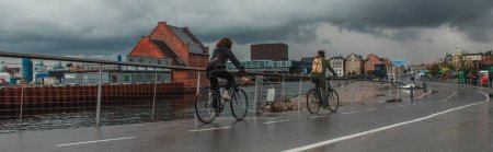 Photo for Panoramic crop of people cycling on urban street near canal with cloudy sky at background in Copenhagen, Denmark - Royalty Free Image