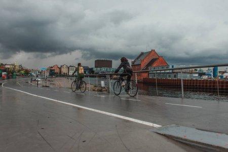 Photo pour Personnes circulant à vélo près du canal dans la rue urbaine de Copenhague, Danemark - image libre de droit