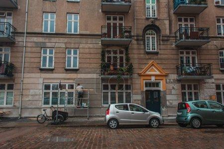 Photo pour Voitures sur la route près de la façade du bâtiment sur la rue urbaine à Copenhague, Danemark - image libre de droit