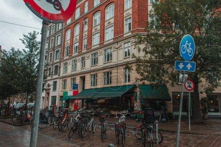Photo pour Concentration sélective des vélos et panneaux de signalisation routière sur la rue urbaine à Copenhague, Danemark - image libre de droit