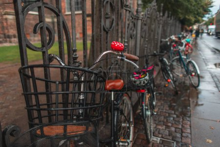 Photo for Selective focus of bikes near fence on wet walkway of urban street, Copenhagen, Denmark - Royalty Free Image