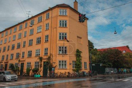 Photo pour Rue urbaine avec route et vélos près de la façade du bâtiment et ciel nuageux en arrière-plan, Copenhague, Danemark - image libre de droit